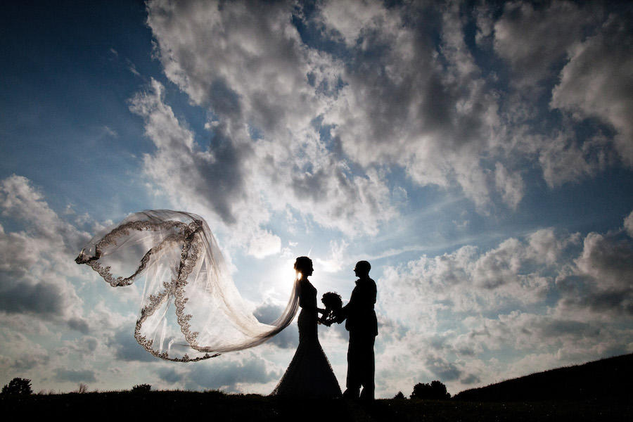 A cloudy sky background for the silhouette wedding image of the couple standing face-to-face holding the bouquet, with the bride's veil flowing in the wind.