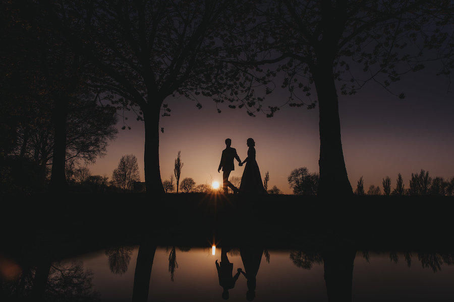 The sun is setting low in the image of the wedding couple holding hands, walking together, as their reflection shows in the water below them.