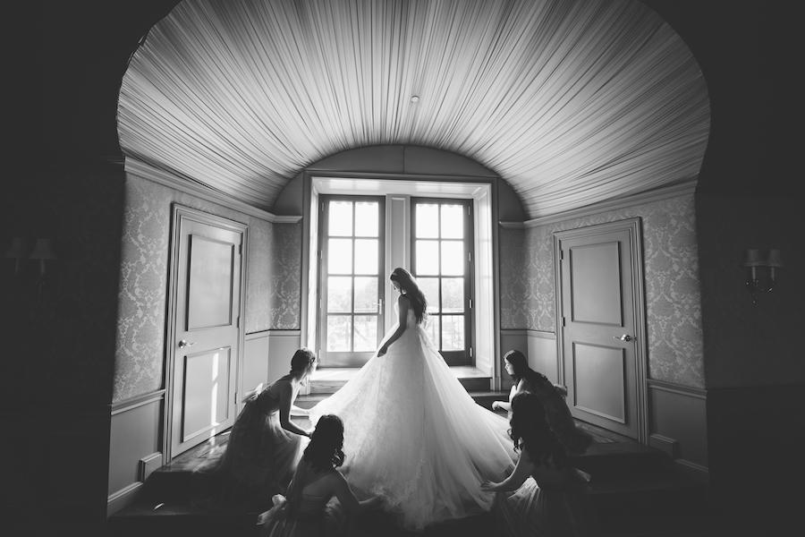 bridesmaids helping with bride's dress