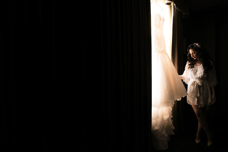 bride next to window with dress