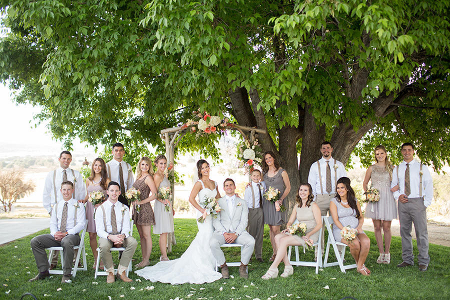 An image of the wedding party together outdoors, under a tree.