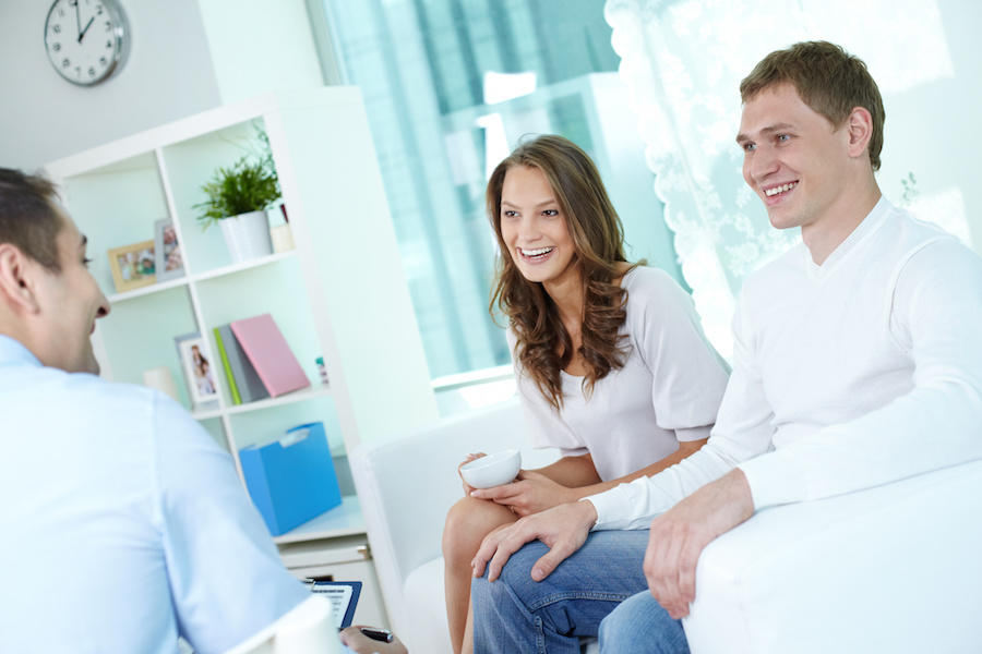 positive young couple at home having a conversation with a smiling business consultant