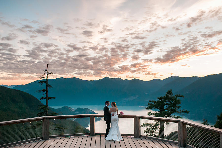 A wedding image with the bride and groom standing at the edge of a balcony with a river and mountains, and a sunset as their background.