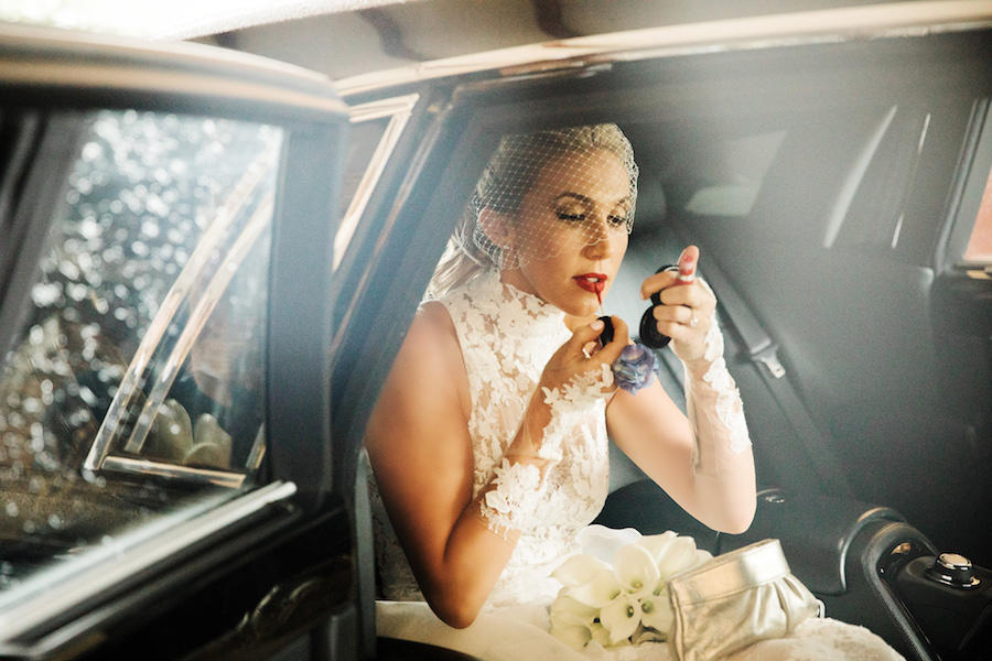The bride with a short veil over her face is sitting a car, putting on her red lipstick with a compact mirror.