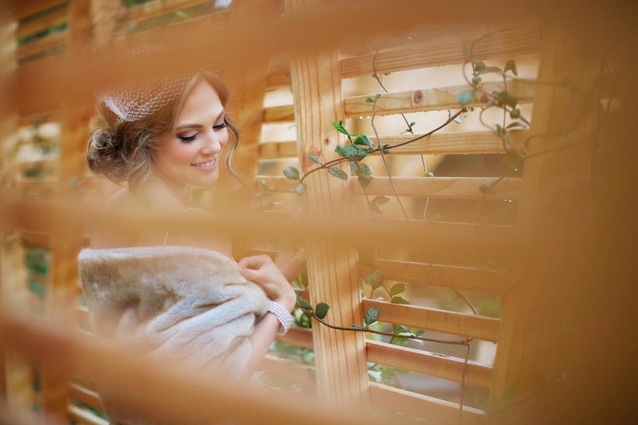 A wedding photo of the bride standing behind a fence and looking toward the side with her eyes partially closed.