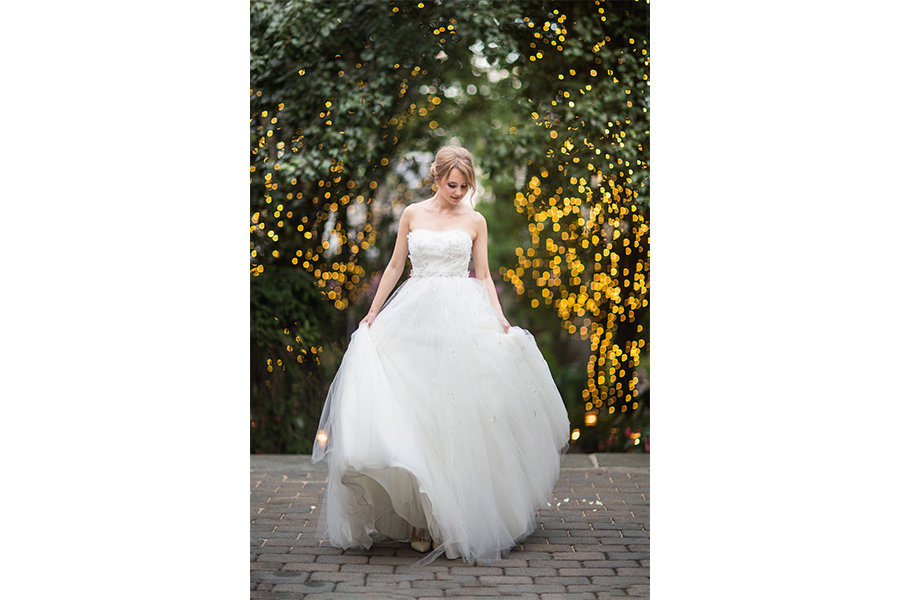 Outdoor bridal portraits with trees that have lights on them blurred in the background, while the bride with blonde hair pulled back holds the sides of her strapless wedding dress and looks down at her left hand.
