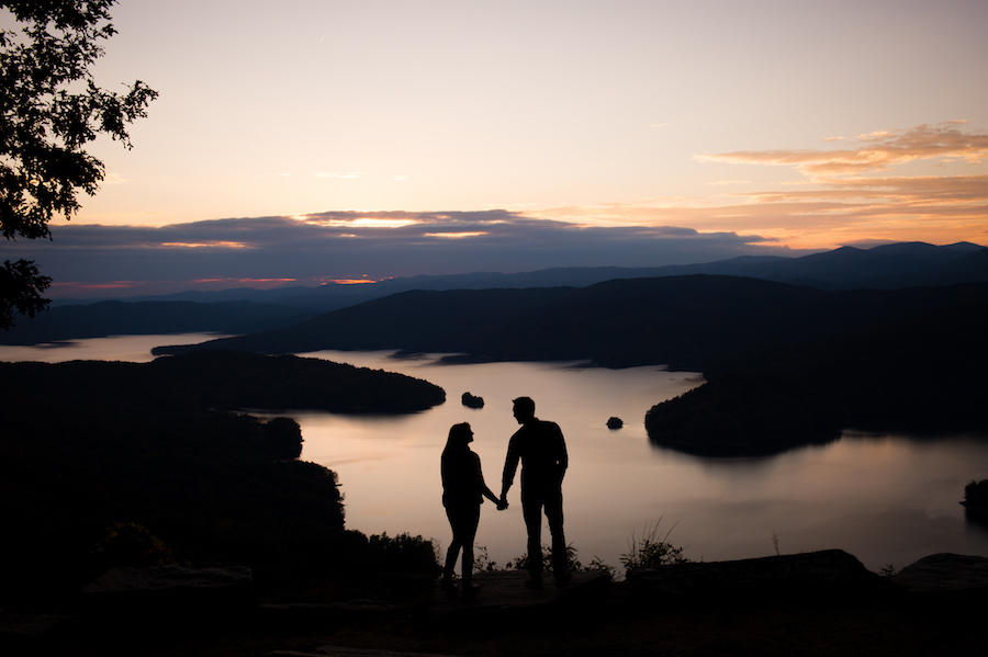 The couple is holding hands and looking toward one another in this wedding silhouette image that is taken in front of a lake with the sun setting low.
