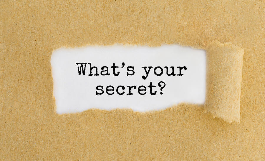 what's your secret appearing behind ripped brown paper