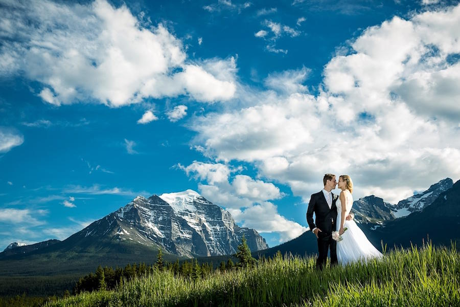 A wedding photo of the bride and groom standing in the grass with mountains, a blue sky, and clouds as their backdrop.