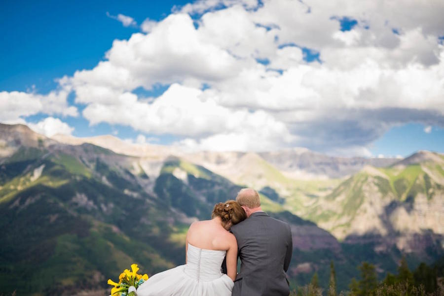 A bride and groom with their backs facing the camera, the bride's head on the groom's shoulder and his head on her head, with an incredible landscape in front of them.