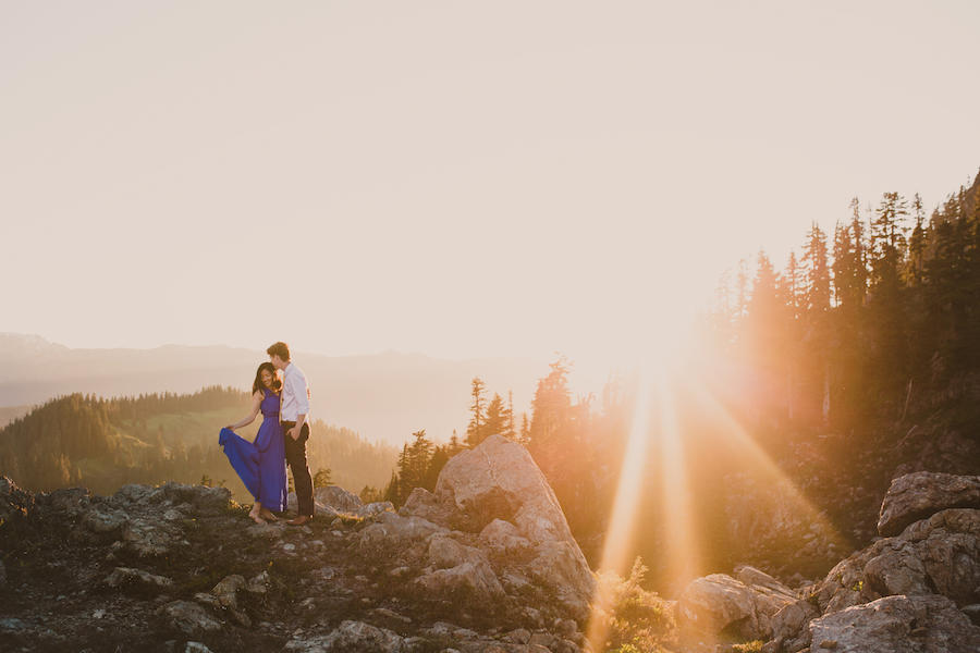 An engagement sunset session where the couple is standing near the edge of a mountain and the bride is holding the side of her blue dress out and the groom, who is kissing her head, is wearing a white button-up and black pants.