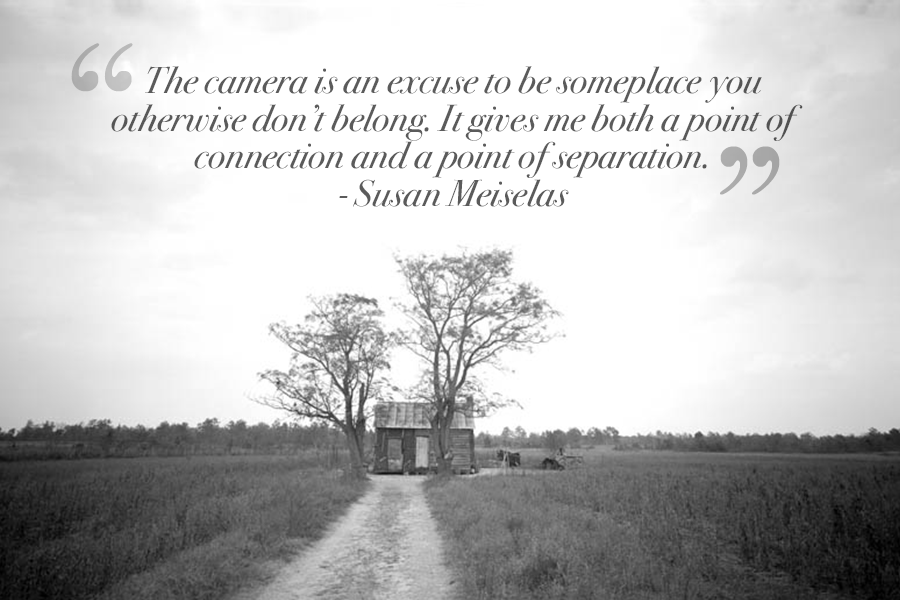 A famous inspirational photography quote by Susan Meiselas on a black and white wide shot of a long road with grass on both sides that leads to a small house surrounded by two tall trees.
