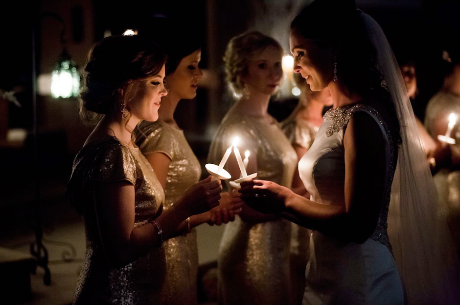 The bride and one of her bridesmaids lighting each other's candles outdoors, while the rest of the bridal part is behind them.