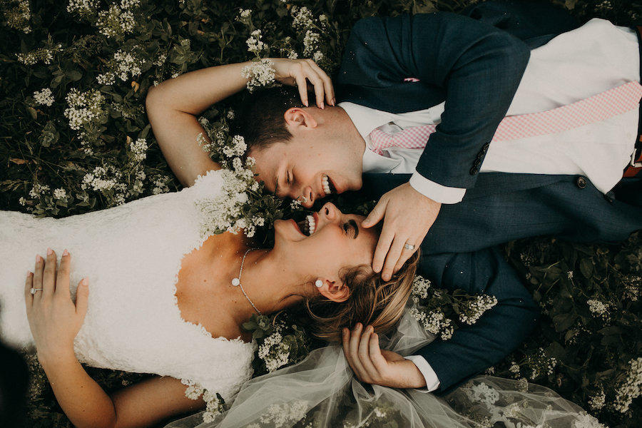 bride and groom laying on flower bed