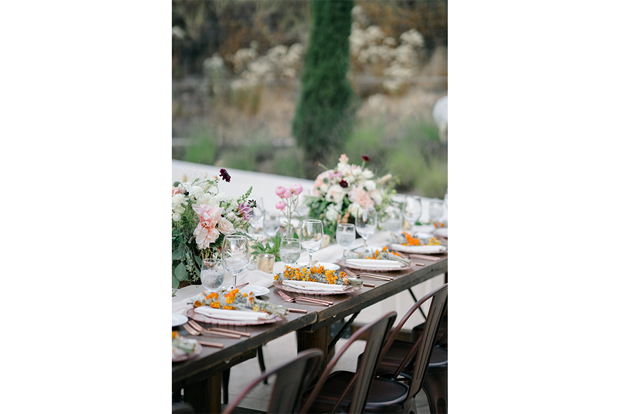 A wedding detail shot of the an outdoor reception table with plates and flowers.