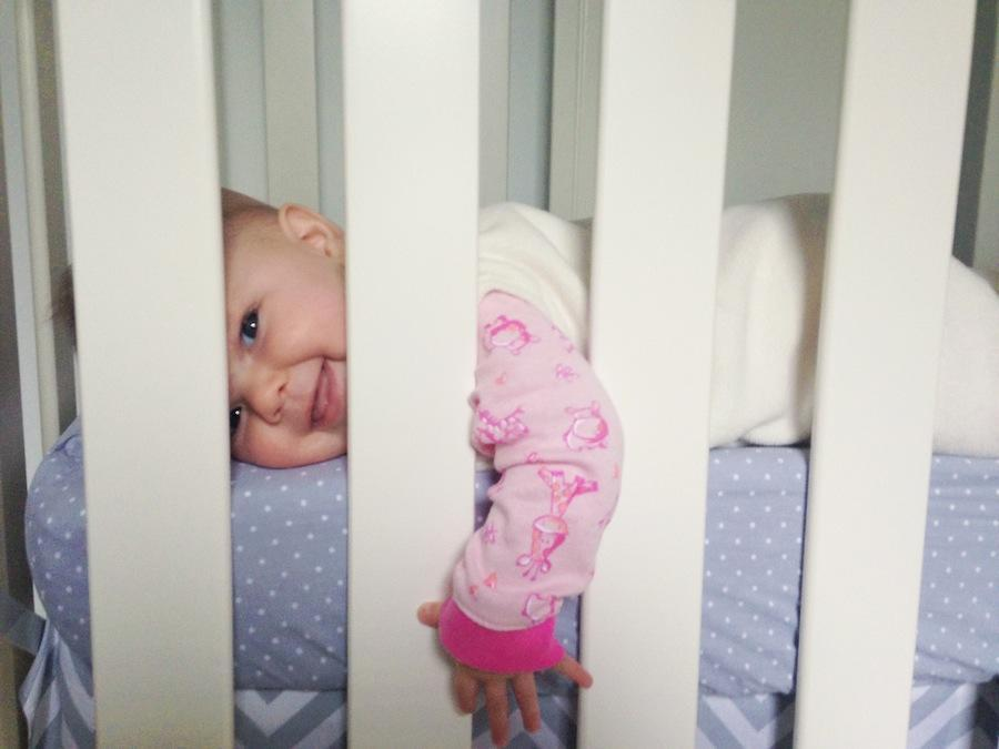 An image by Leeann Marie of her daughter laying in her crib and facing the camera.