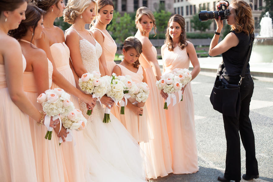 A behind-the-scenes photo of Leeann Marie as she takes photos of the wedding bridal party outdoors.
