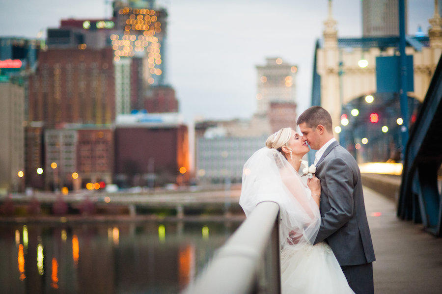 A wedding photography couple portrait outdoors with a blurred background of the city.