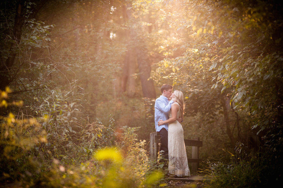 An outdoor engagement session with sunlight shining through the trees on the couple facing one another & kissing.