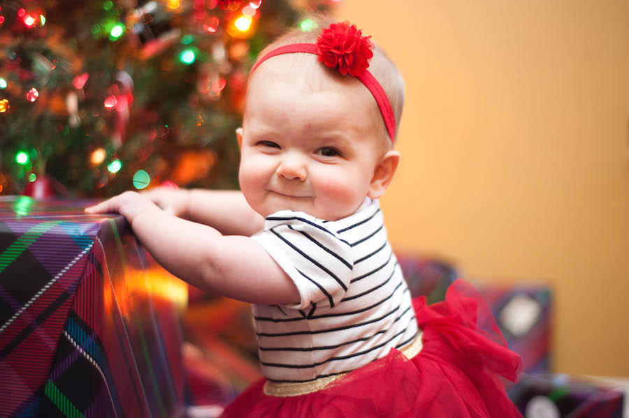 An image by Leeann Marie of her daughter holding a present with a Christmas tree blurred in the background.