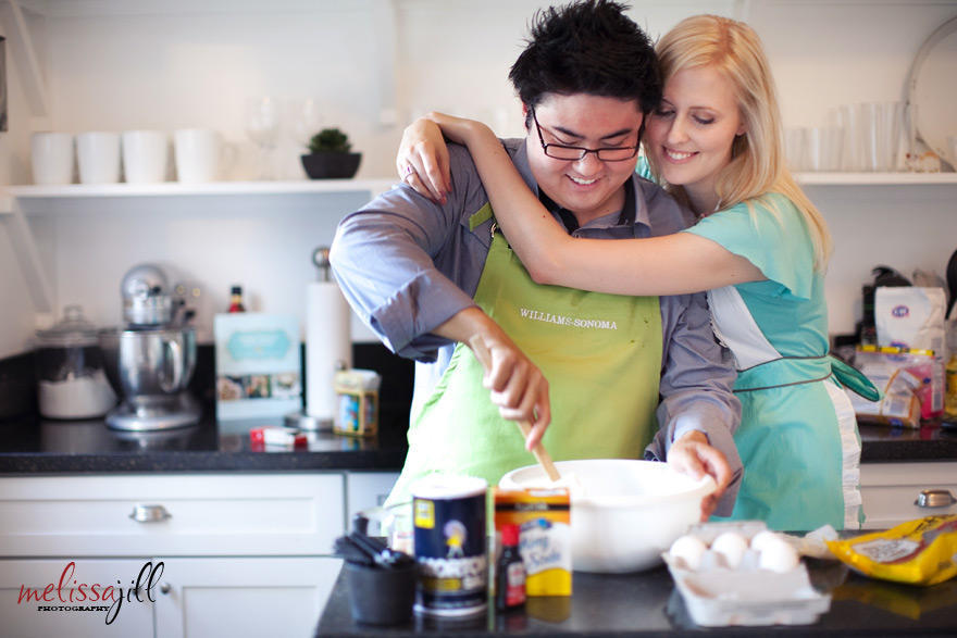 An indoor engagement session in a kitchen with the couple baking together, with the woman's arms wrapped around the man's shoulders as he stirs ingredients in a bowl.