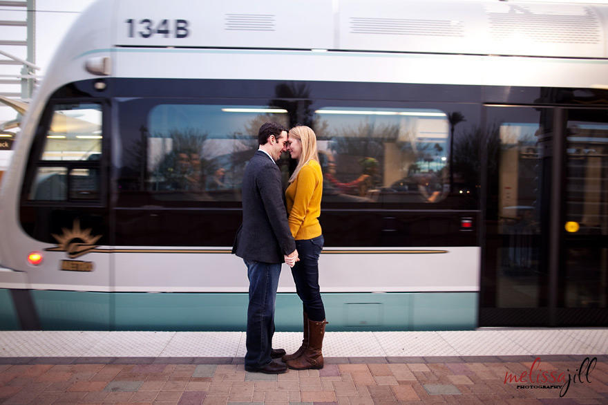 A couple standing nose-to-nose in front of the Phoenix light rail, with their hands interlocked.