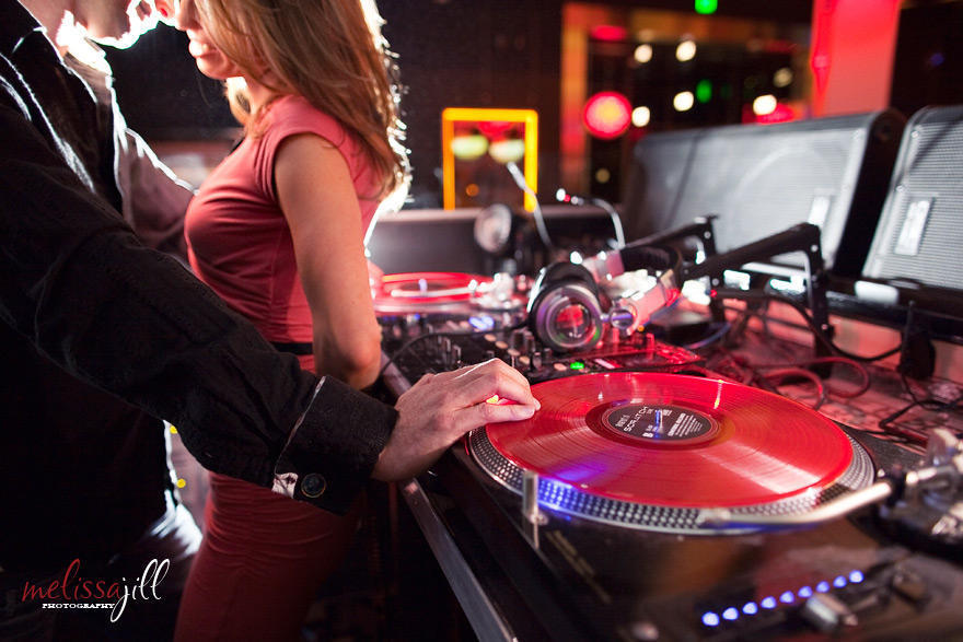 A couple facing one another, with the woman's back against a DJ booth and the man's hand on a record.