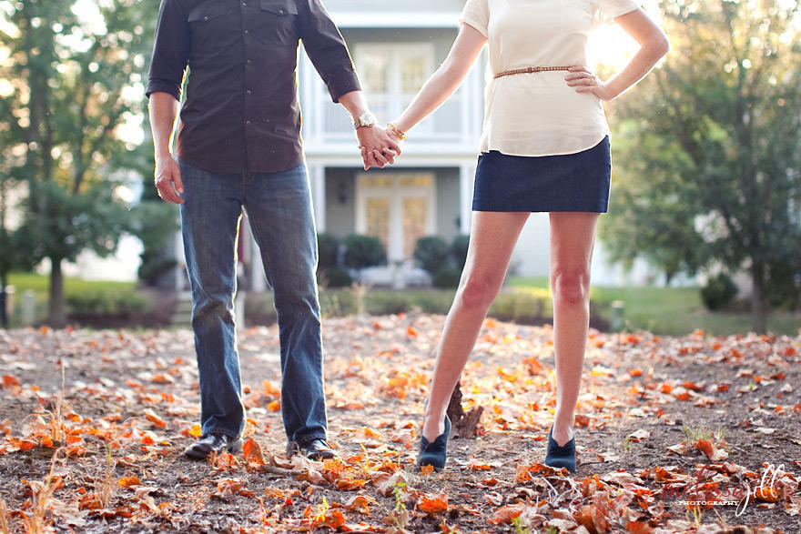 A photo of a couple holding hands, with the camera cut off at their chests, with leaves fallen on the ground and natural light in the background.