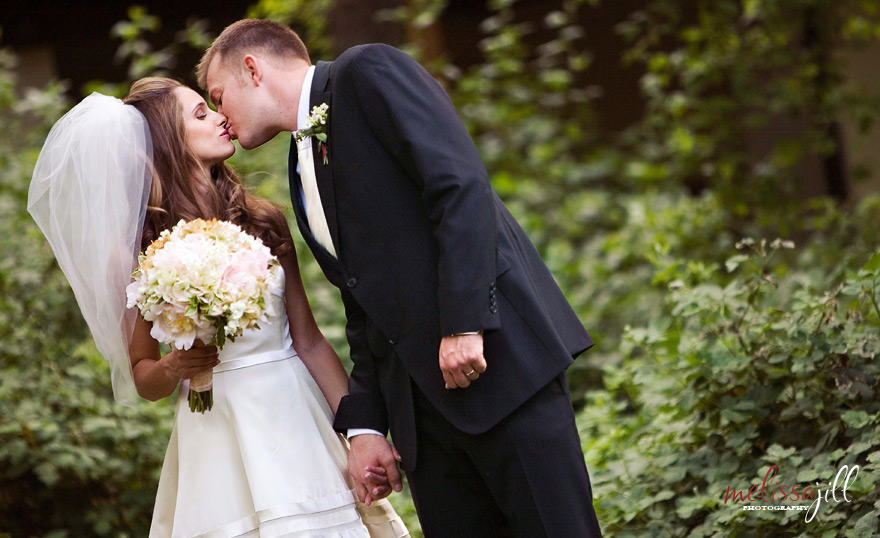 Bride and groom kissing, while the bride holds her bouquet in one hand and holds the groom's hand with the other.