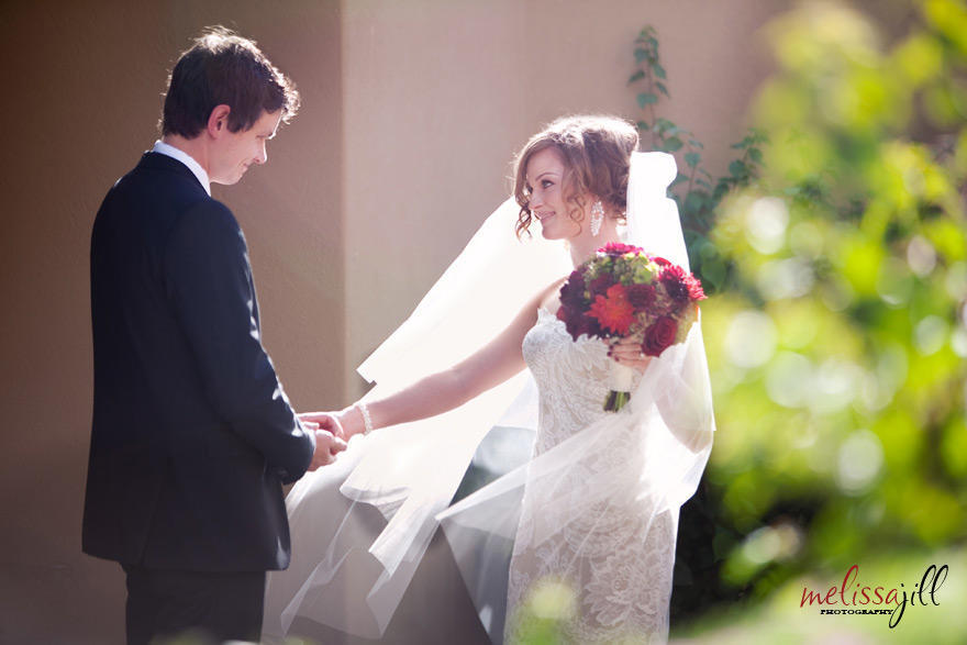A wedding photography image with the bride and groom looking at one another, with the groom holding the bride's right hand, while her left hand holds her bouquet.
