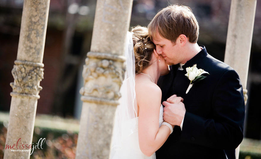 A wedding photo of the bride and groom dancing, with the groom's face resting on the side of the bride's face.