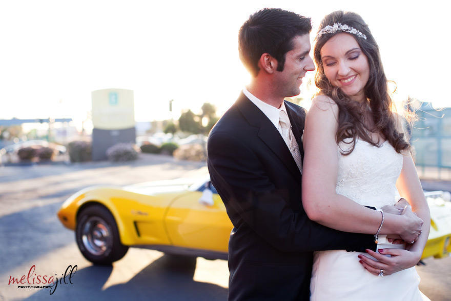 An outdoor wedding photography image of the bride and groom in an embrace, with the groom's yellow Corvette in the background behind them.