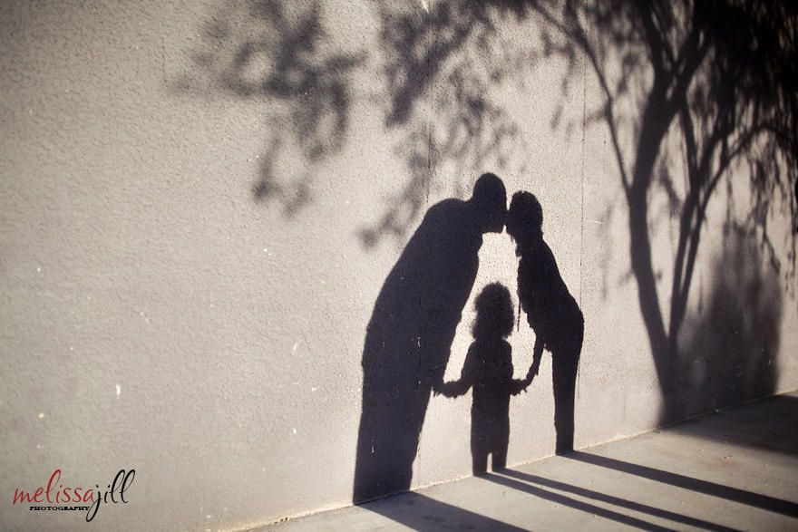 A family photography image of the couple kissing with their child in the middle as a shadow on a wall outdoors.
