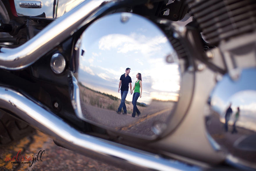 A reflection on a motorcycle of a couple holding hands and walking during their engagement session photos.