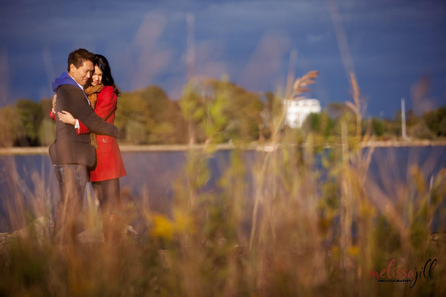 A couple embracing during their engagement session photos, with tall grass in the foreground and blue water and sky in the background.