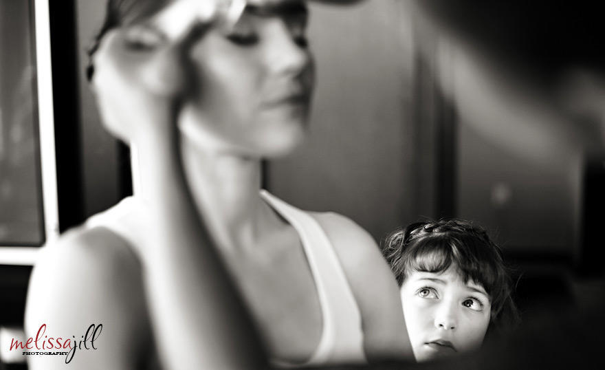 A black and white wedding photography image of the bride getting her makeup done, while a young girl watches from the side.
