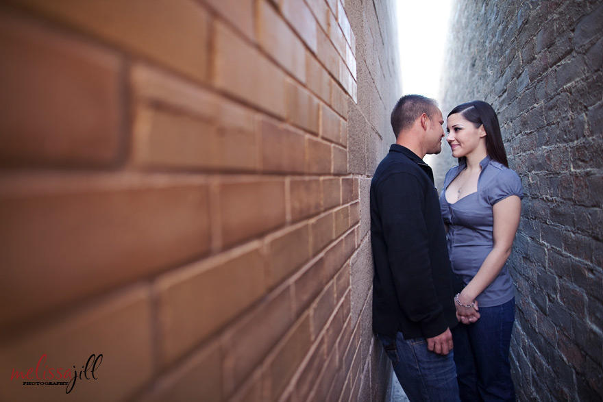 Couple in an engagement session in between two walls in an alley (ordinary places to take pictures near me/you) facing one another & holding one hand.