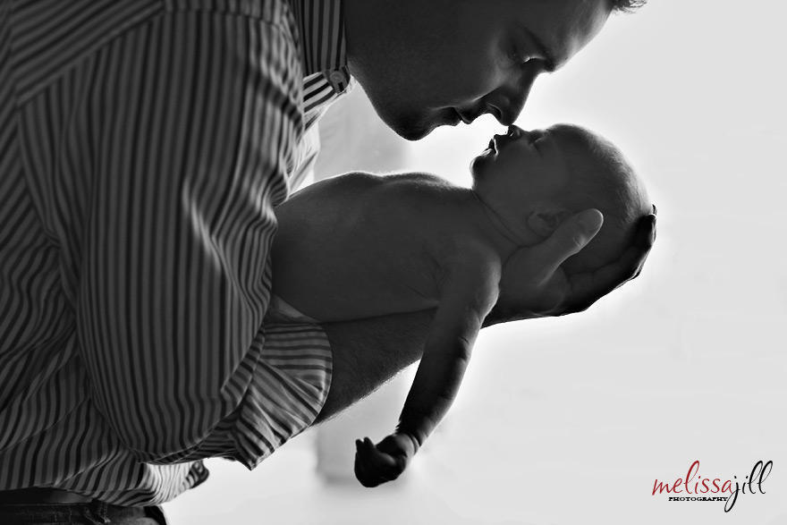 A black and white image of the side a father holding his newborn baby in his arms.