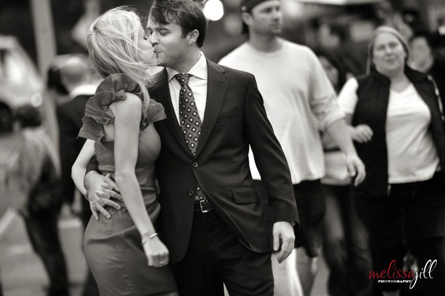 A black and white photo of a couple kissing during their engagement session in New York City on a crosswalk.