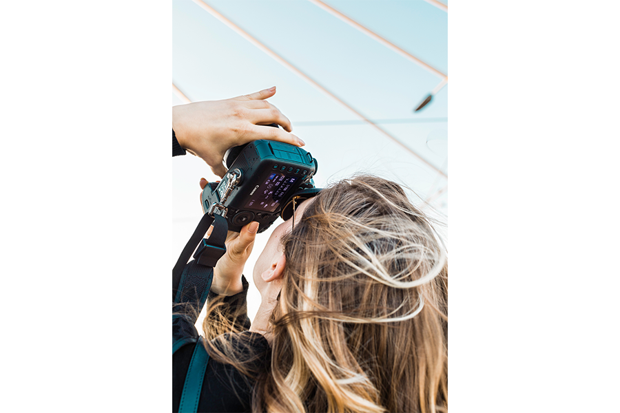A woman holding a Canon DSLR up toward the sky.