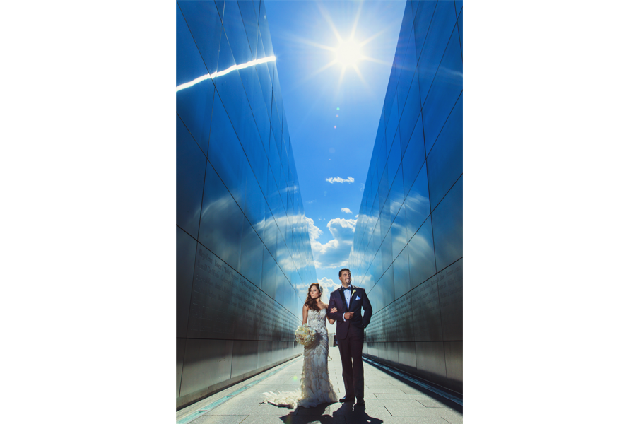 An image of the couple standing side by side, arms interlocked, in between a blue building, with the bride holding her bouquet and the sun shining on them.