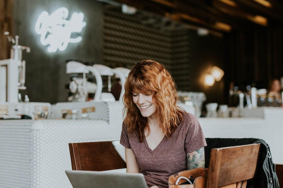 An image of a woman with red hair and arm tattoos in a coffee shop, smiling and looking down at the laptop in front of her.