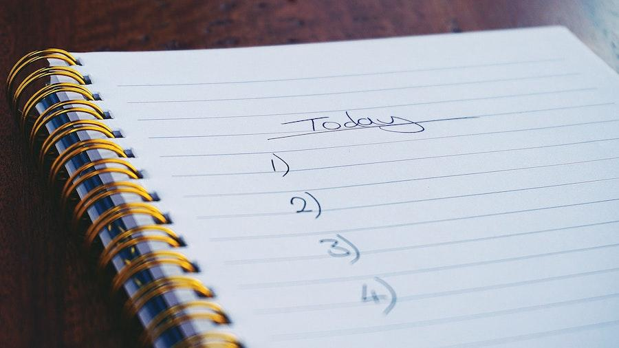 "An image of a notebook on a brown flat surface with the word ""Today"" and the numbers 1 through 4 listed as a to-do list."