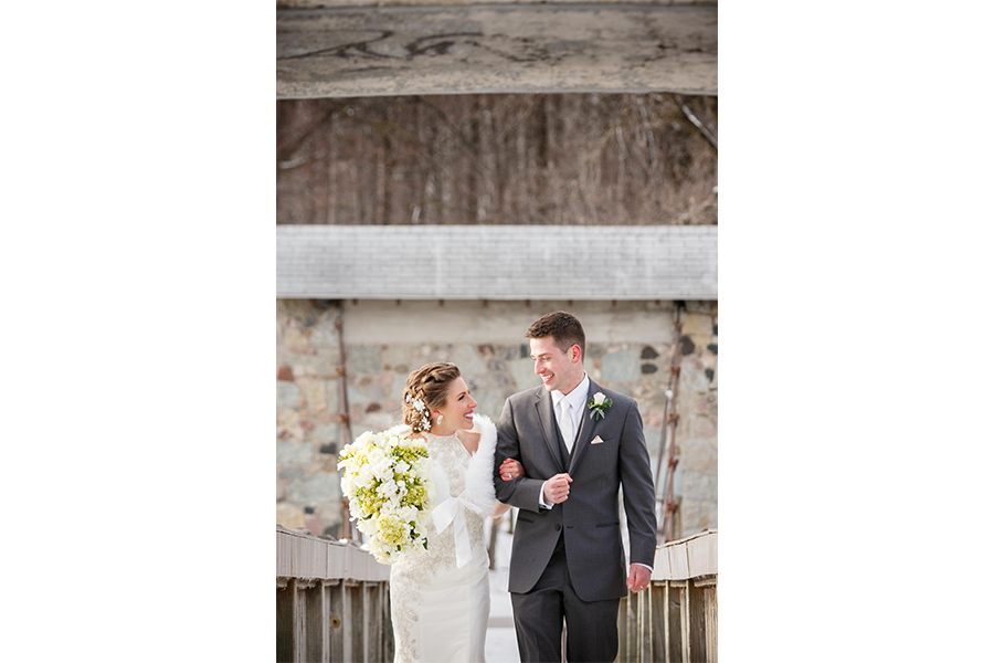 A vertical outdoor winter wedding photo of the bride and groom, arm in arm and looking at one another, as they walk upstairs.