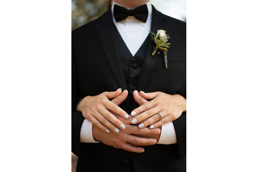 A wedding photography image of the front of the groom and his tux, with the bride's hands over his hands.