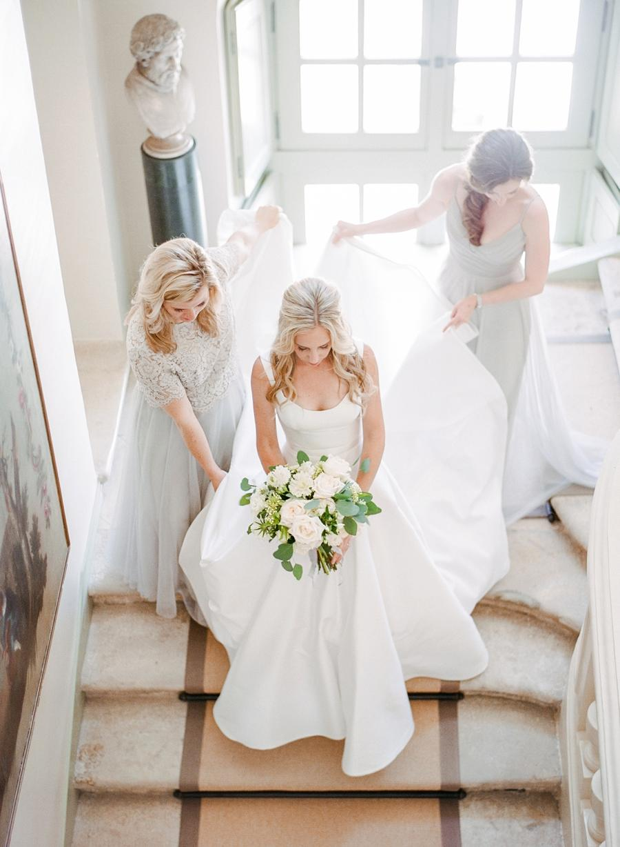 A bride walking down the stairs with a bouquet in hand & bridesmaids holding her dress