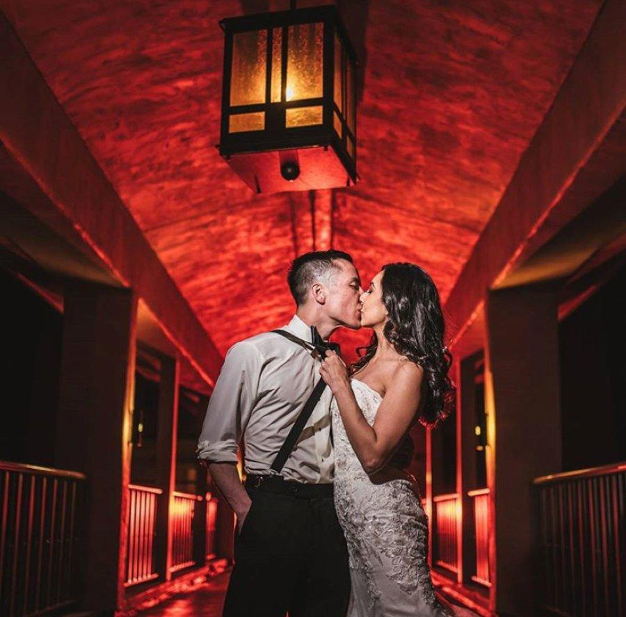 Bride and groom kissing in front of a red-lit background