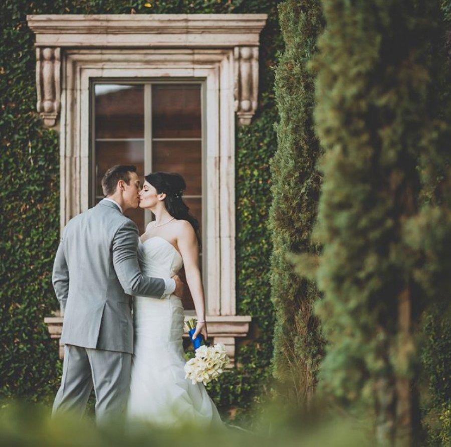 Bride and groom posing in front of a window