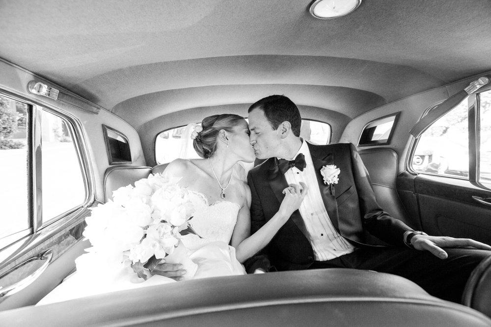 A black and white image of the bride and groom inside a car