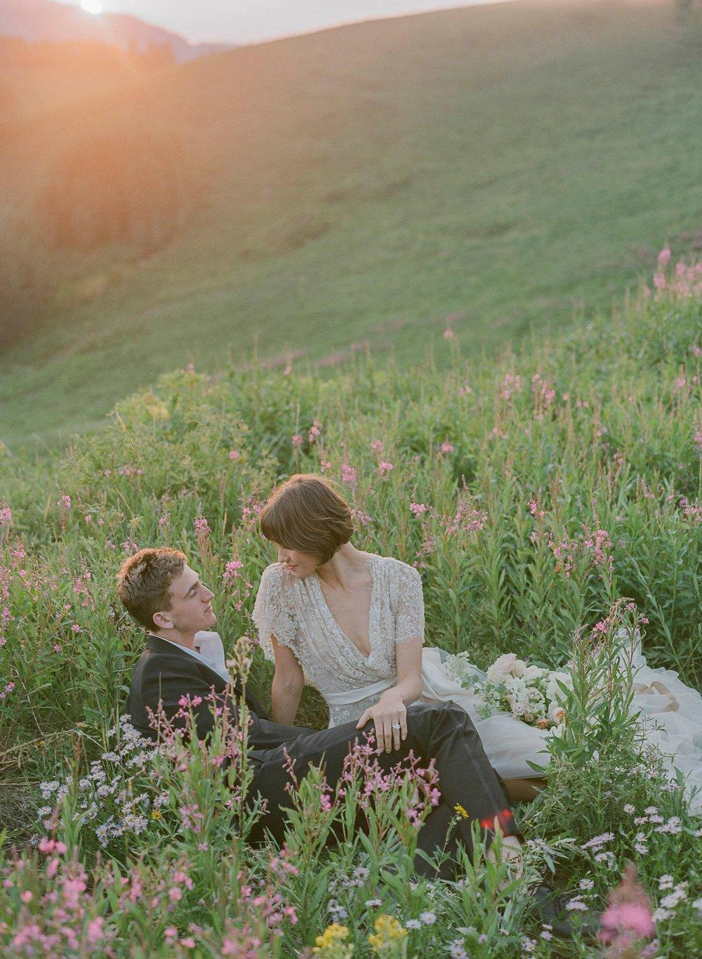 A cinematic shot featuring a couple surrounded by flowers and greenery - Laura Murray wedding photography metrics
